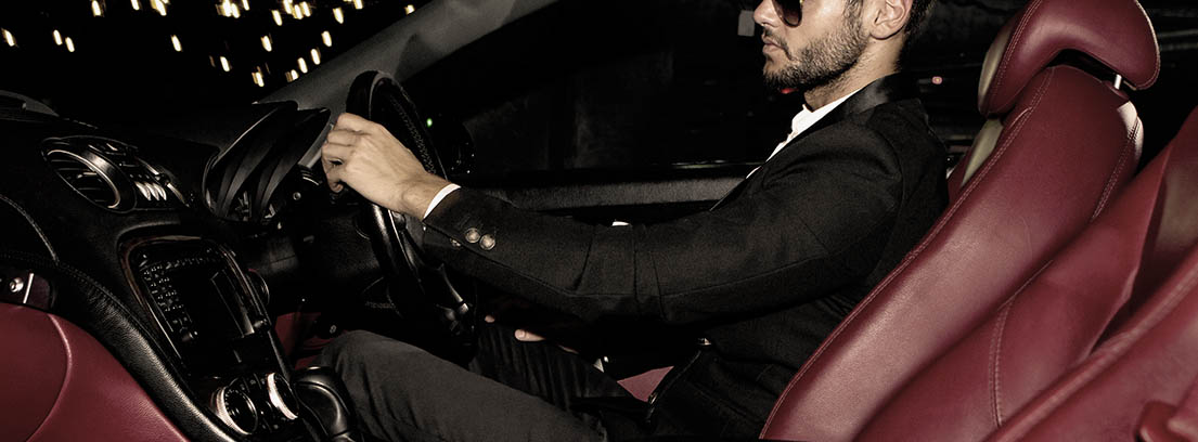 Man in a suit and sunglasses driving a prestige vehicle